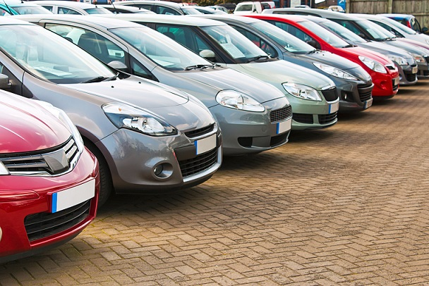 Line up of various types of used cars for sale on a motor dealers forecourt all marques removed